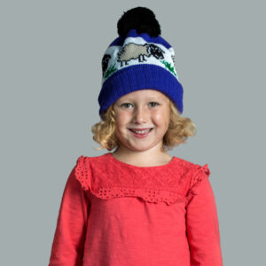 Girl smiling wearing a knitted bobble hat with a sheep on it.