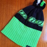 Hope Technology green and black custom logo beanie with a stripe pompom.