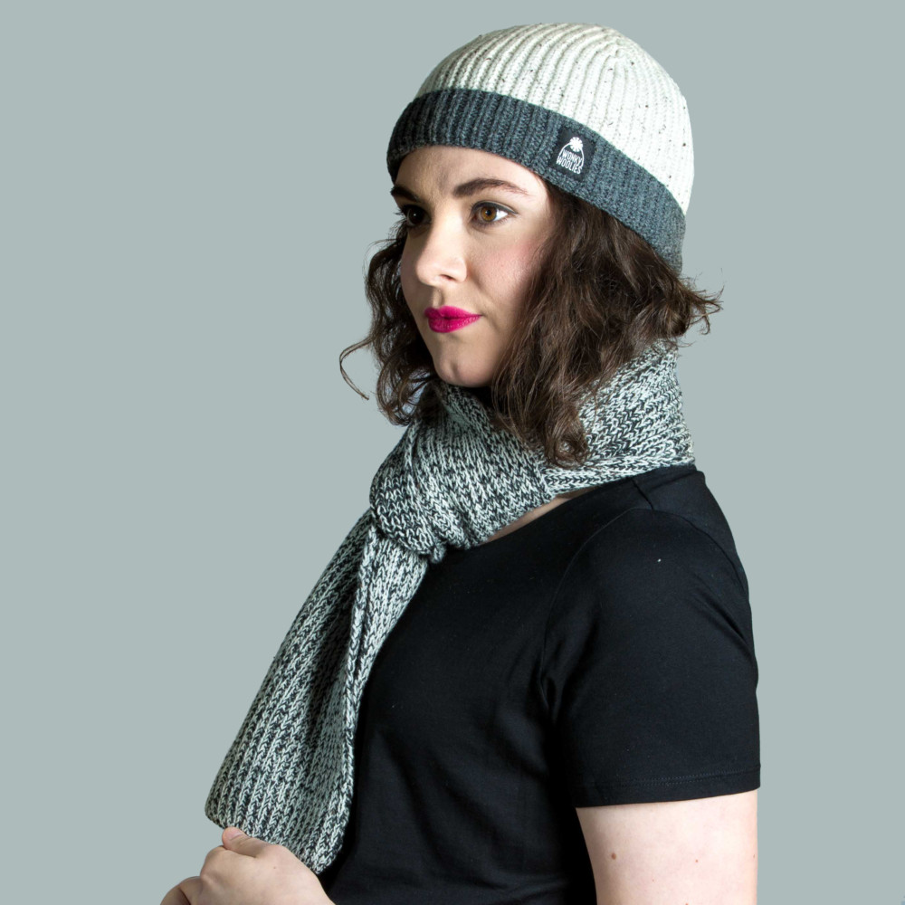 Female model wearing a knitted hat and scarf set.