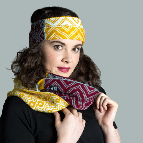 Model wearing knitted headband and infinity scarf in acrylic yarn.