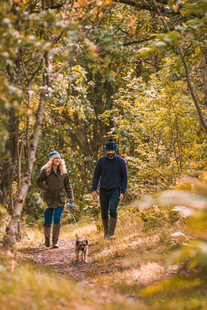 Man and woman on a Spring walk with their dog through the woods.