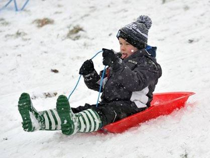 Little boy sledging wearing his bobble hat and wellies.