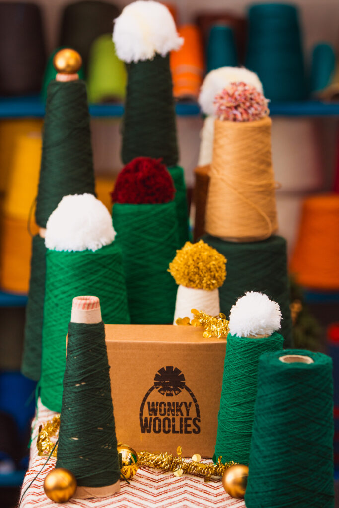 Cones of yarn and pompoms displayed as Christmas trees.